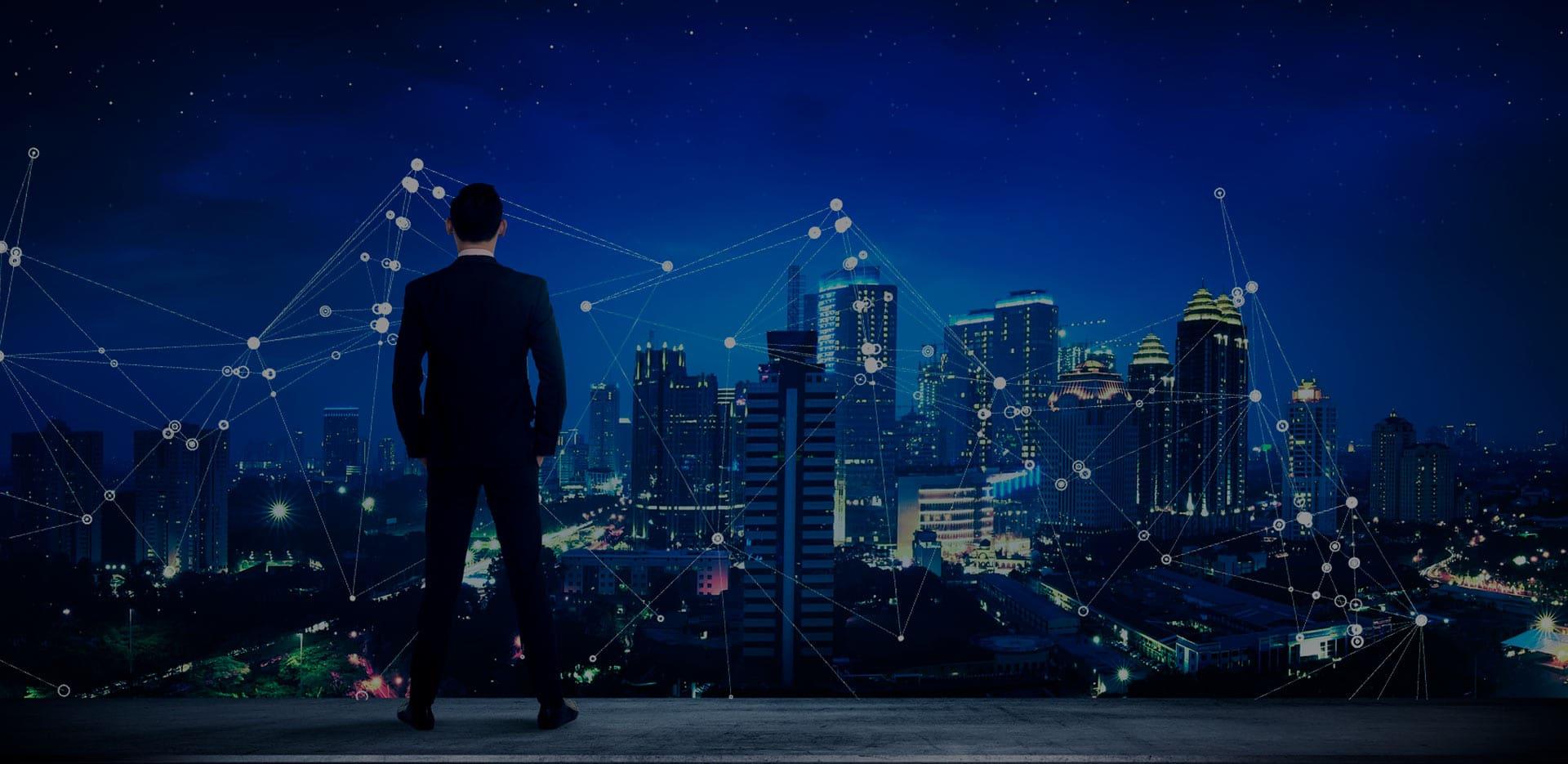 Executivo de terno olhando o horizonte de uma cidade à noite no topo de um prédio